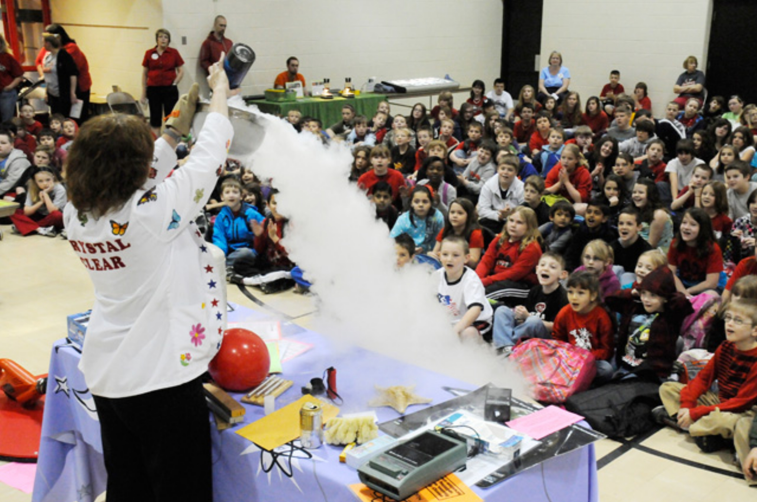 """- Skool Aid is partnering with crystalclearscience.com during the 2018-2019 school years to offer the following programs:May The Force Be With You - This program teaches big ideas in energy, forces, magnetism, electricity and motion, with an eye-popping demonstration that will leave you wanting more!Sounds Like Fun - A fast-paced program, filled with audience participation, as we learn about pitch, volume and the science of sound! Kids will learn several fun experiments they can try at home!Wonderful Water - Kids will be surprised to find out what they don't know about sinking and floating as they participate in an interactive group experiment. View the """"magical"""" demonstrations in surface tension that kids can easily reproduce at home and will have them talking bout this program all year!Weather Wonders - Sun, air, water…and so much more! Awesome demonstrations of air pressure, lightning and thunder will jumpstart kids' understanding of the world around them. Experiments in Bernoulli's principle, static electricity, and the water cycle inspire the meteorologist in all!Steam Powered Recycling - Empower kids by letting them know they can CHANGE THE WORLD! This program teaches students where things come from and where they go. Electromagnets, generators, lasers and change of state demonstrations help kids see the science, technology, engineering and math that go on behind the scenes.Math and Science Connection - A bed of nails, a wondrous windbag, and magic divers will teach your kids that science and math are the best of friends! The power of measurements and and numbers come to life during this program. Kids will be excited to realize they already know many of the math and science connections around us!"""