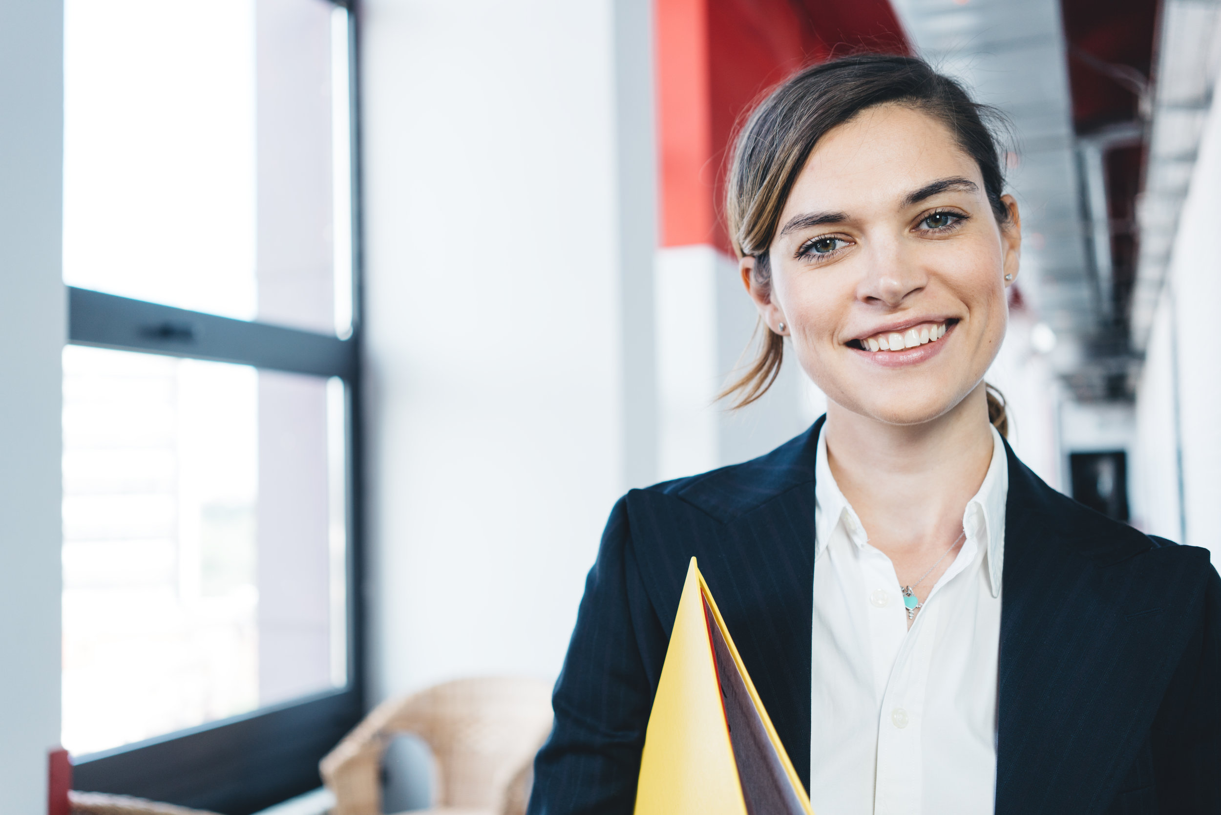 Portrait of smart casual dressed charming business woman with paperwork standing in the office