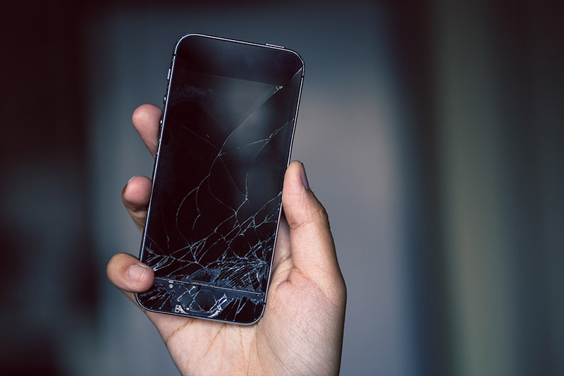 A hand holding a smart phone with a cracked screen in need of phone screen repair in Philadelphia, PA