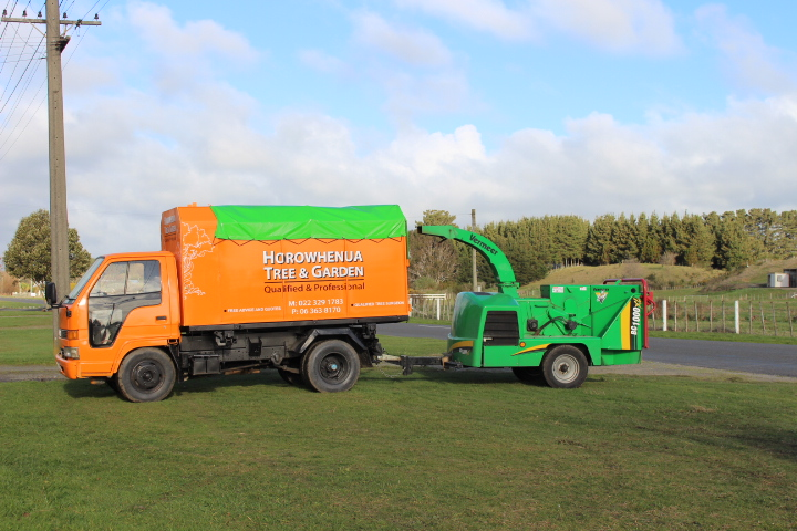 Our bright orange mulch truck and the big green wood chipping machine.