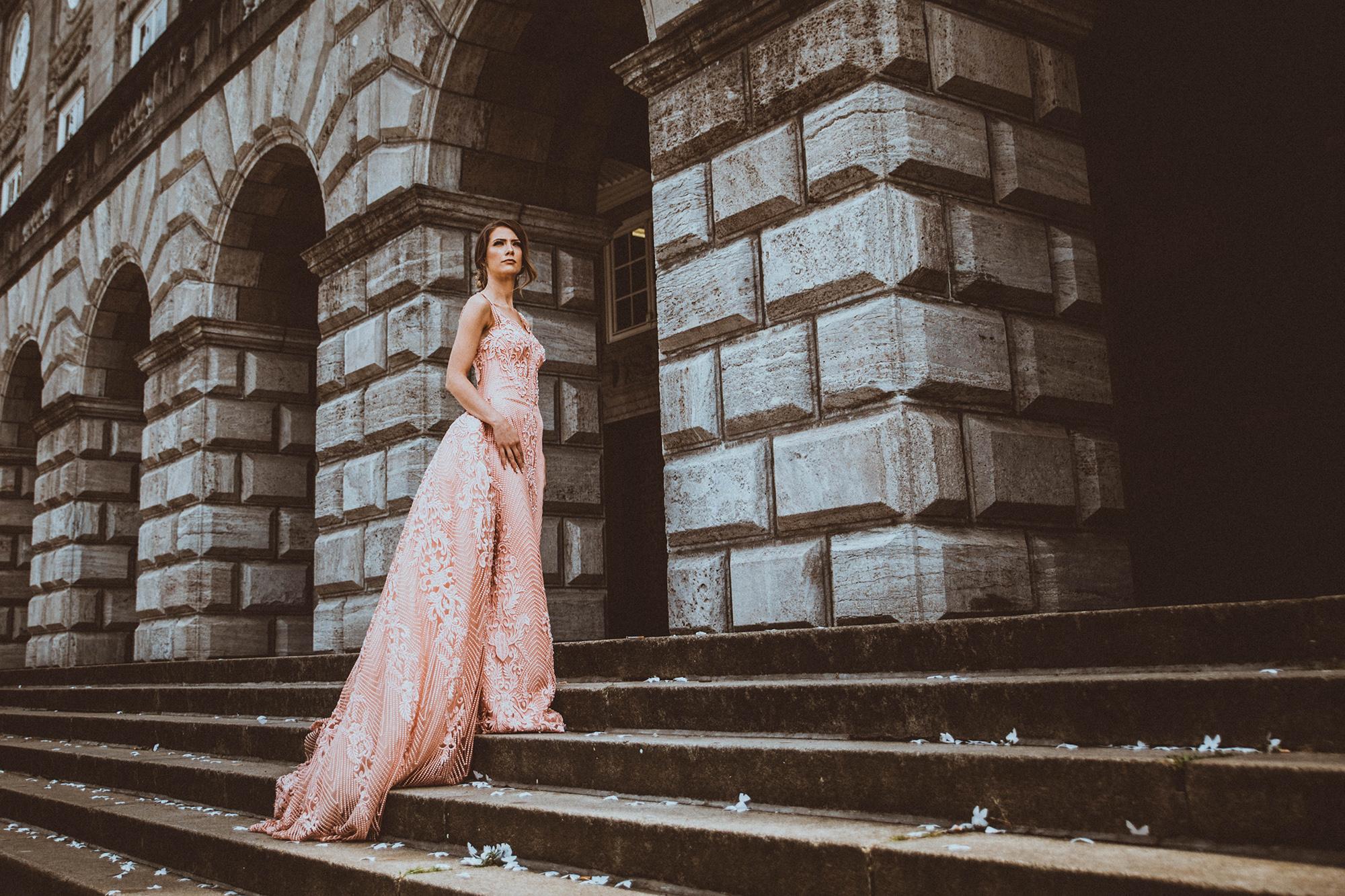 Braut im rosa Kleid, posiert vor ein Steinmauer.jpg