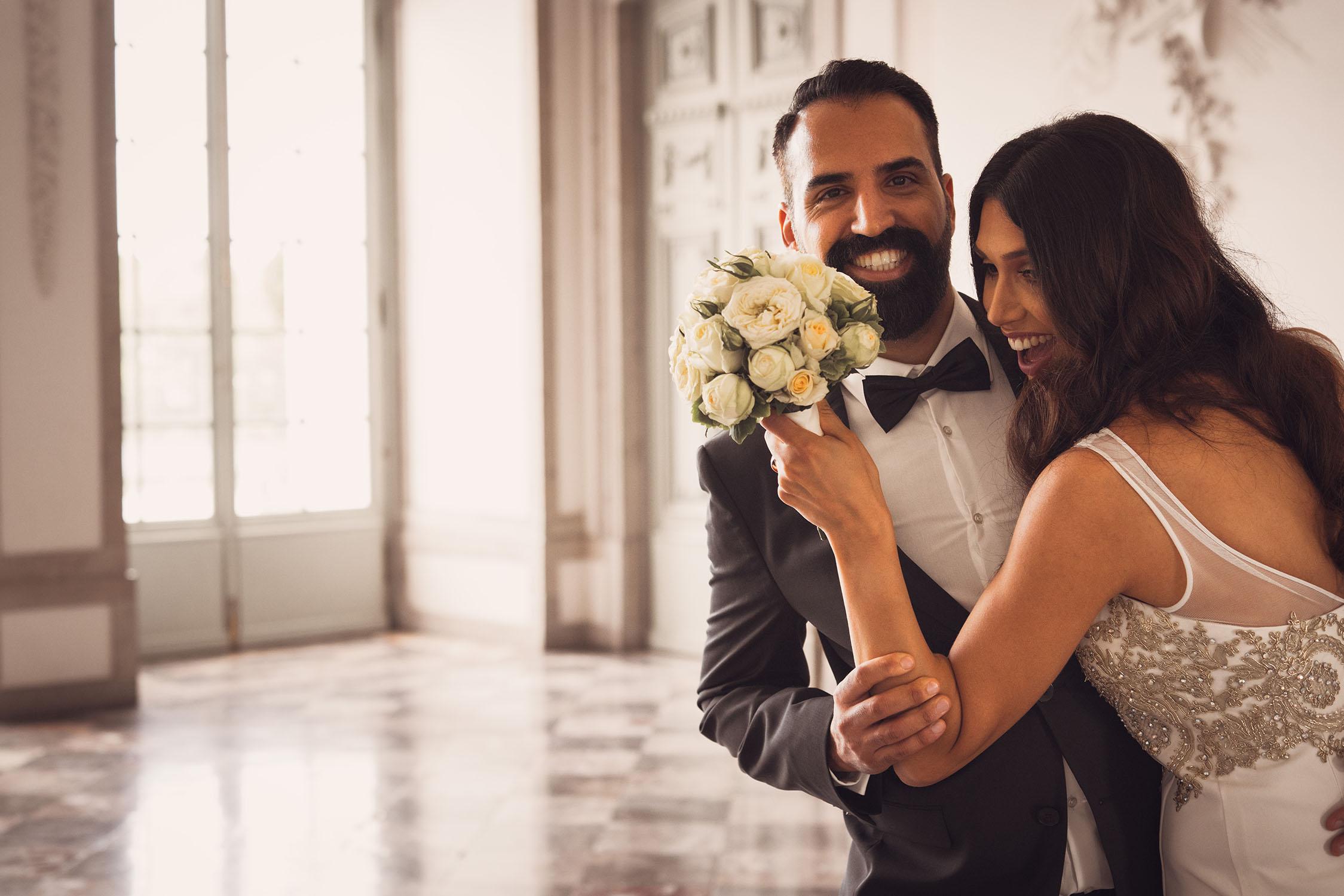 Braut mit Blumenstrauß umarmt Bräutigam.jpg