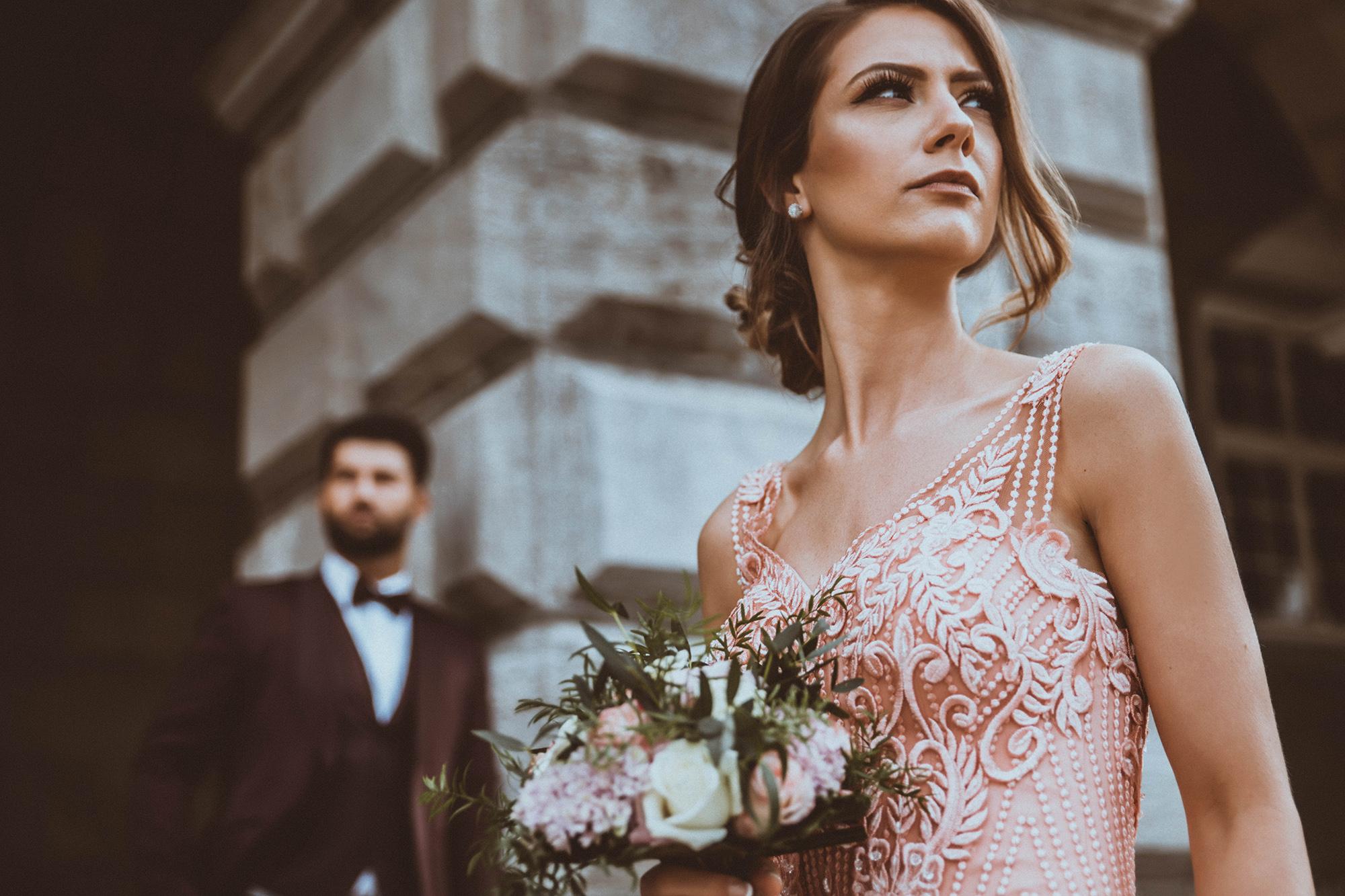 Braut mit Blumenstrauß vor Steingebäude.jpg