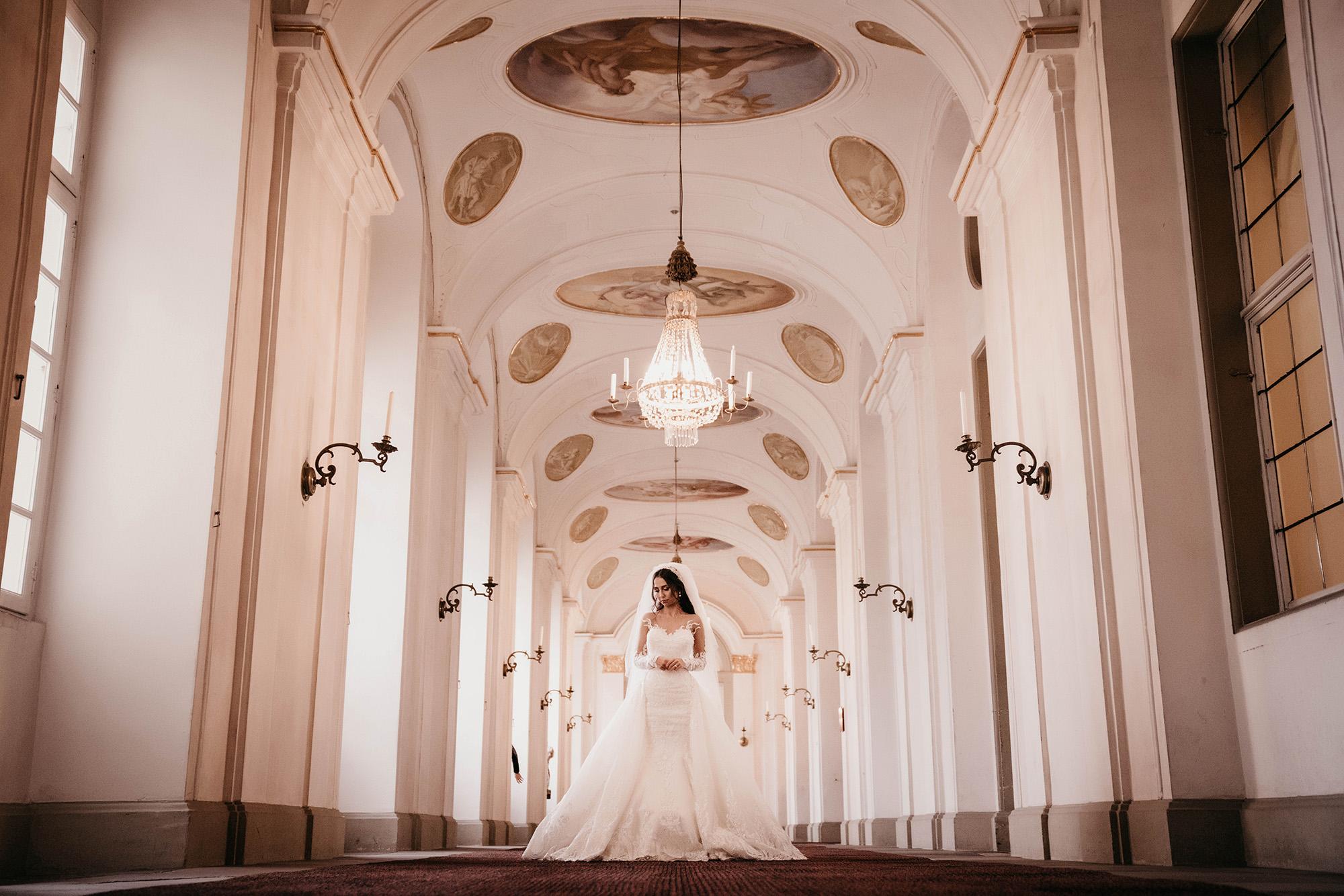 Braut steht unter einer Kronleuchter.jpg