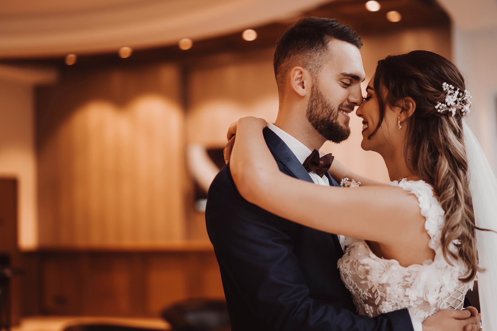 Braut und Bräutigam umarmen einander mit einem Lächeln.jpg