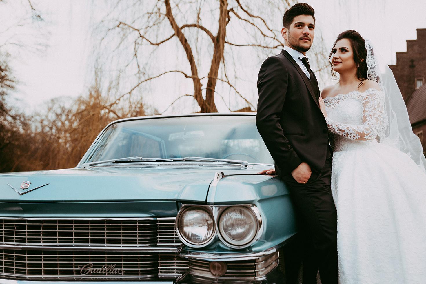 Braut und Bräutigam, die auf blauem Auto sich lehnen.jpg