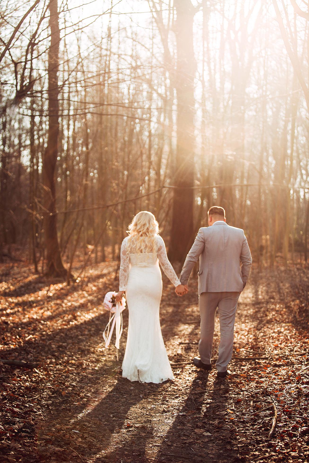 Braut und Bräutigam, die zwischen den Bäumen gehen.jpg