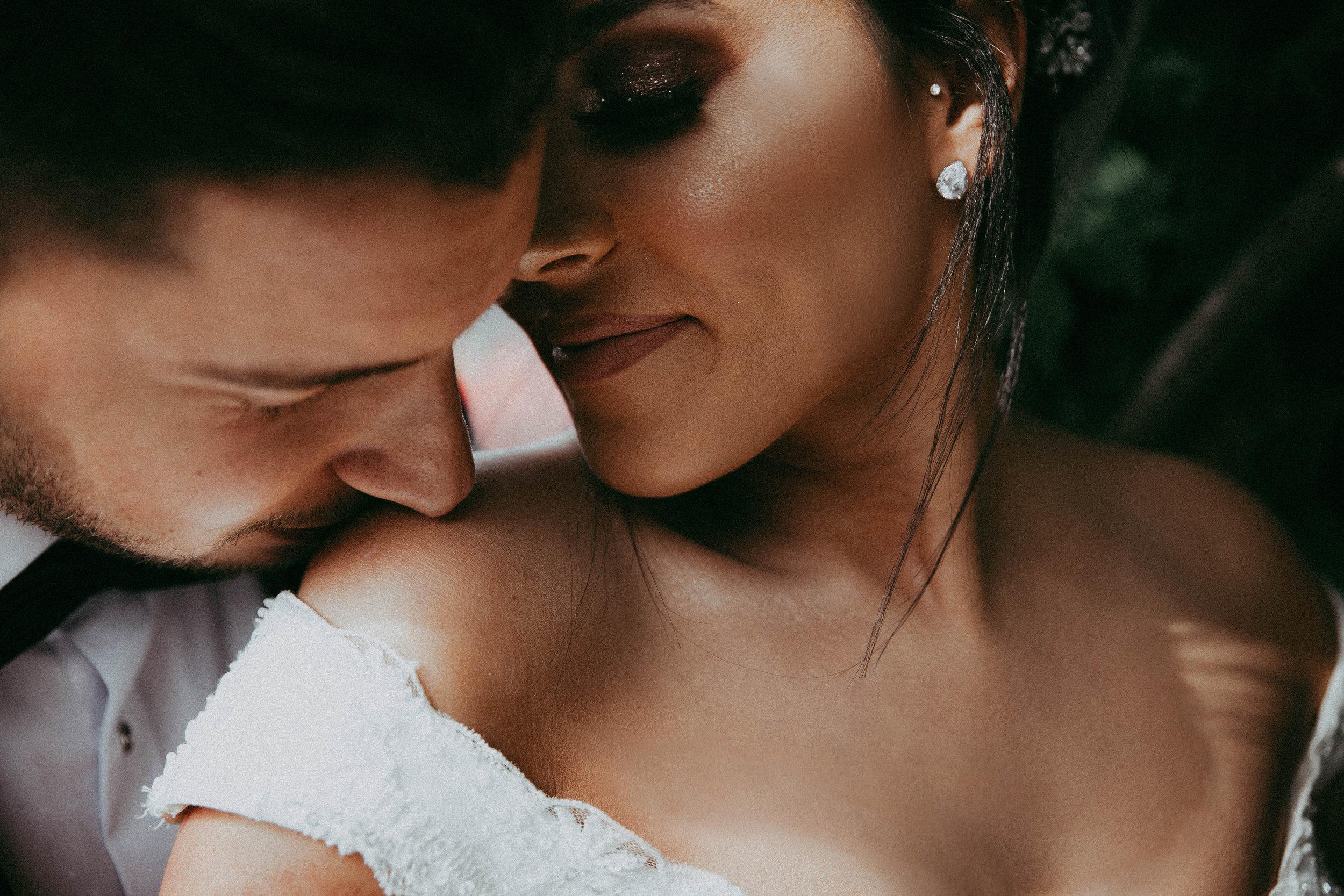 Bräutigam, der Braut auf Schulter küsst.jpg