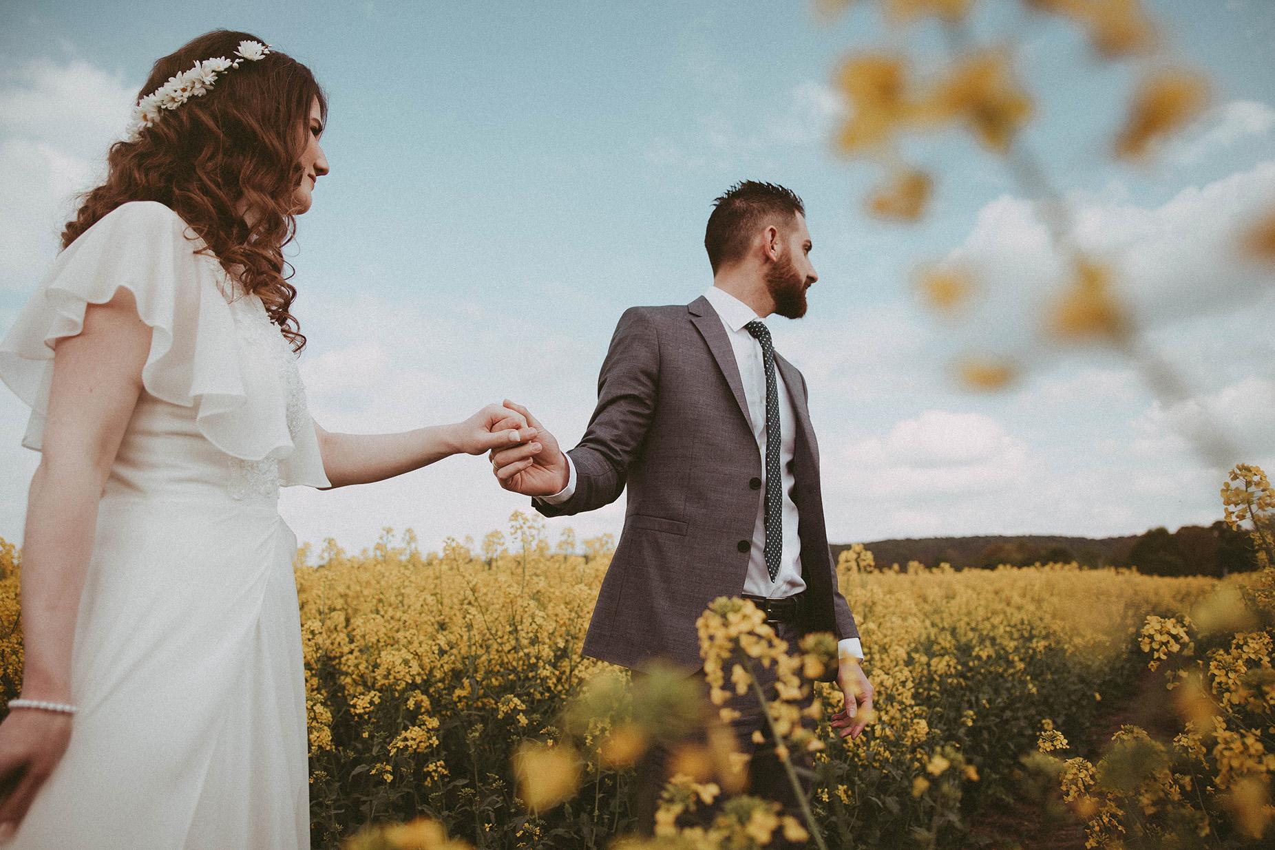 Brautpaar Hand in Hand im Feld mit gelben Blumen.jpg