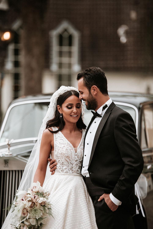lächelnde Braut und Bräutigam vor Rolls-royce.jpg