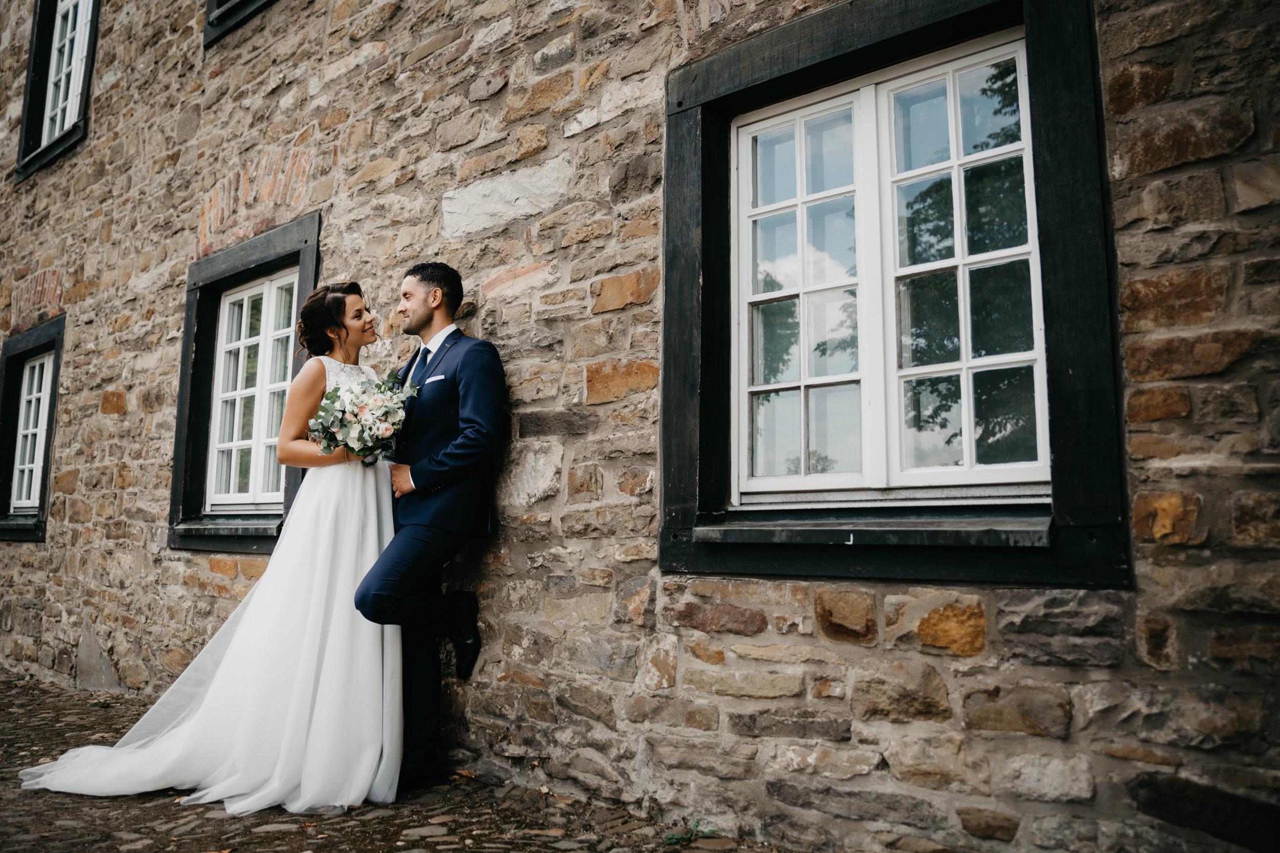 Rustikale Hochzeit, Braut und Bräutigam stehen vor einer Steinwand.jpg