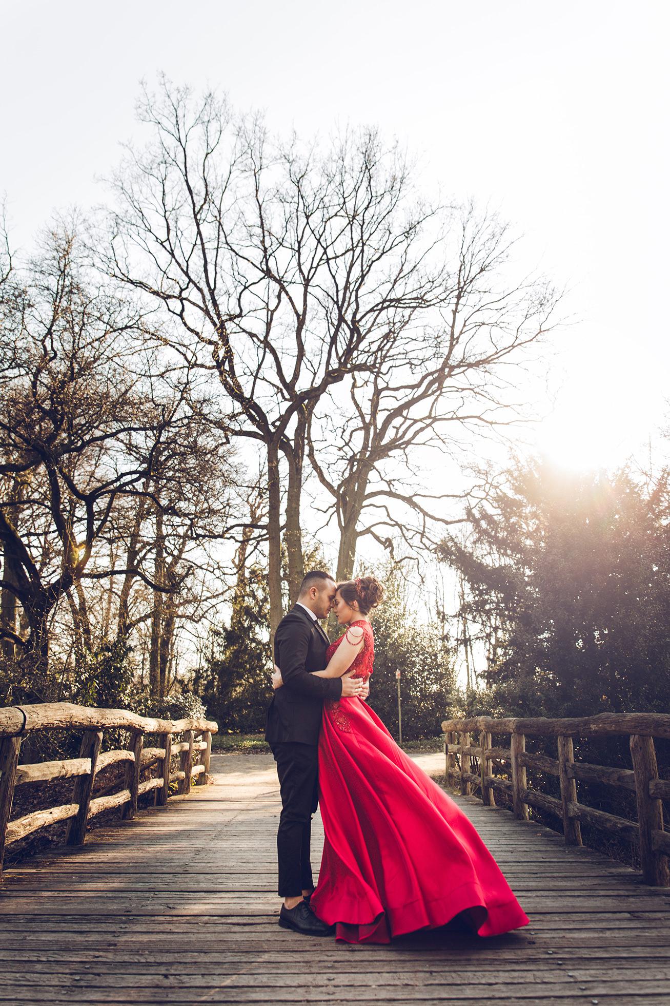 Verlobter umarmt seine Braut im roten Kleid auf der Brücke.jpg