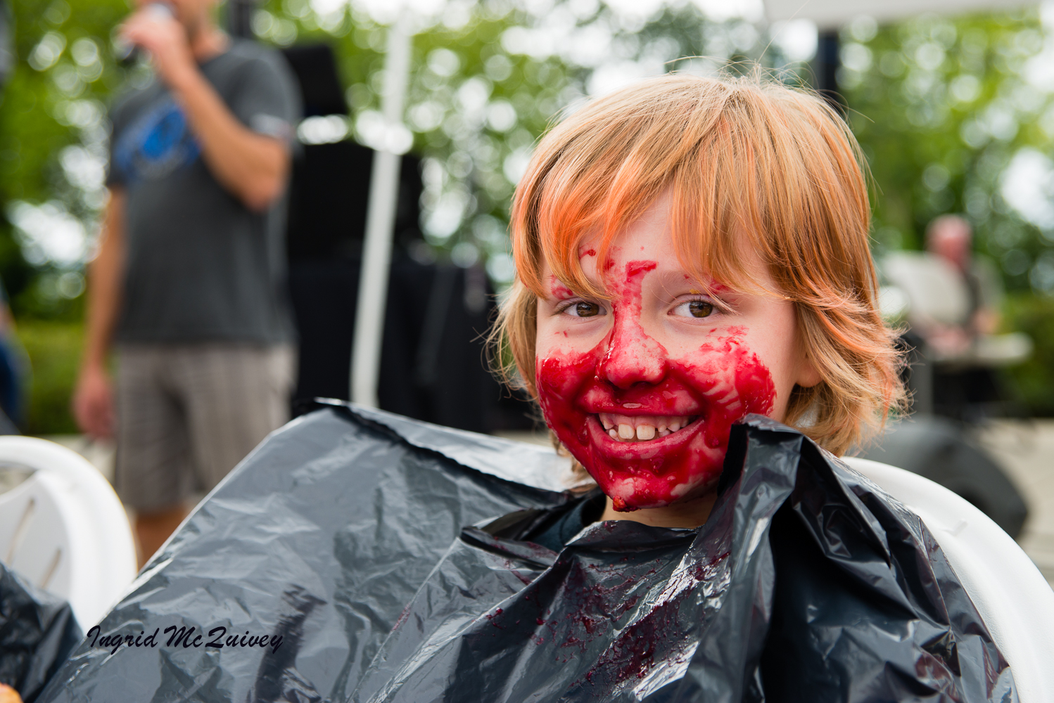 A BOY HAD JUST FINISHED A PIE EATING CONTEST AT THE RED, WHITE, AND BLUE FESTIVAL. THE FESTIVAL IS HELD THE FIRST SATURDAY EACH JULY.