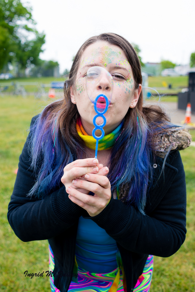 A girl at Riverview Park entertains children with face painting and bubbles. -