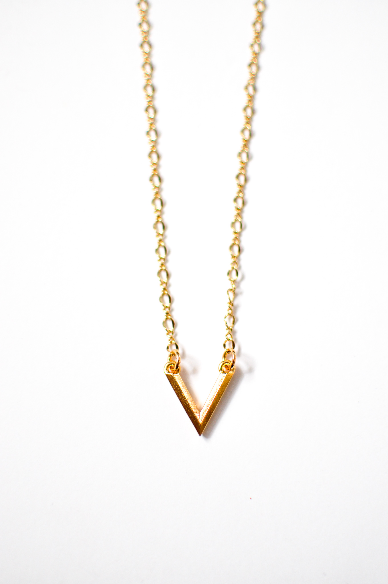 simple gold triangle geometric necklace created by indie twenty jewelry. get the spring and summer beach layering trend.