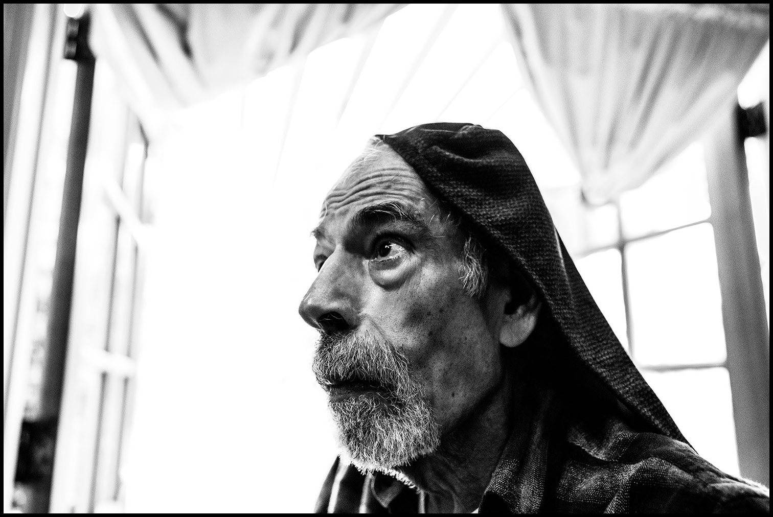 November 1st, 2017: Papa sits next to the french doors leading to the backyard in his home prior to having a meal. He wears the recliner chair protective arm cover on his head. This is something he would do on occasion. - from  Personality Crash: Portraits of My Father Who Suffered from Advanced Stages of Parkinson's Disease, Dementia and Sundowner's Syndrome.