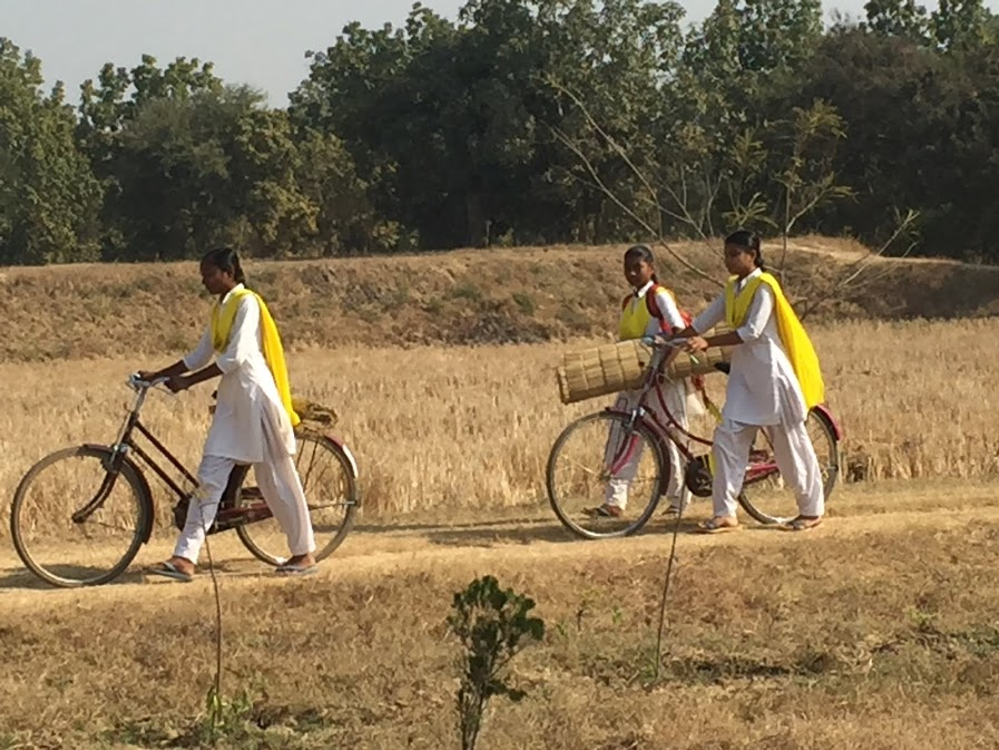 Here the girls are arriving at the school grounds with their bikes.