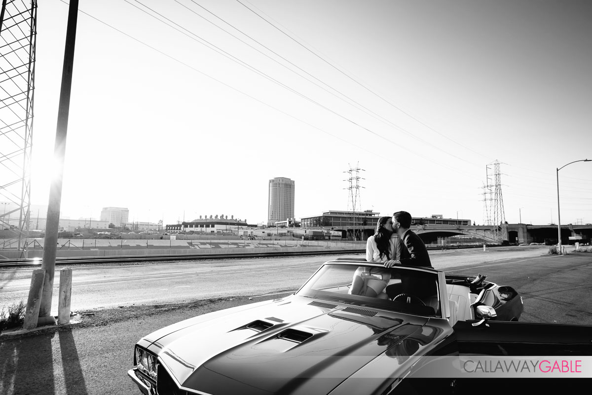 Black and White engagement photo in old car overlooking downtown Los Angeles