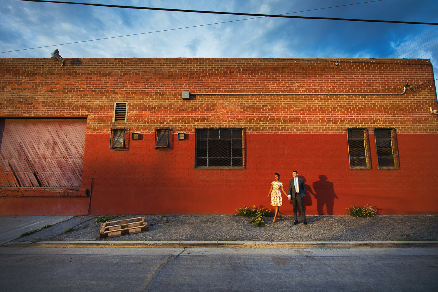 LA warehouse district engagement photo of African American couple against red wall