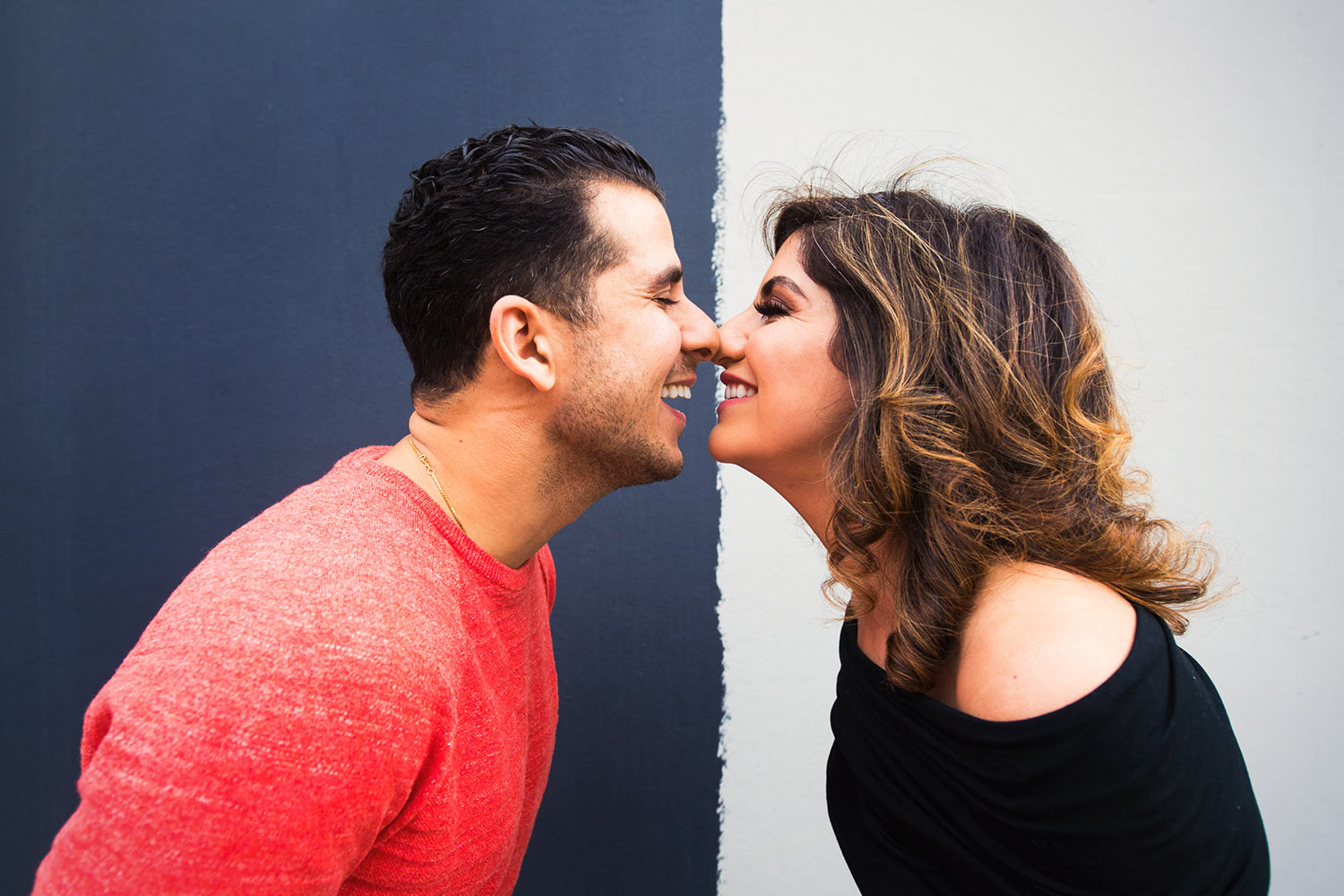 Graphic and fun engagement photo in front of Black and white wall in Los Angeles