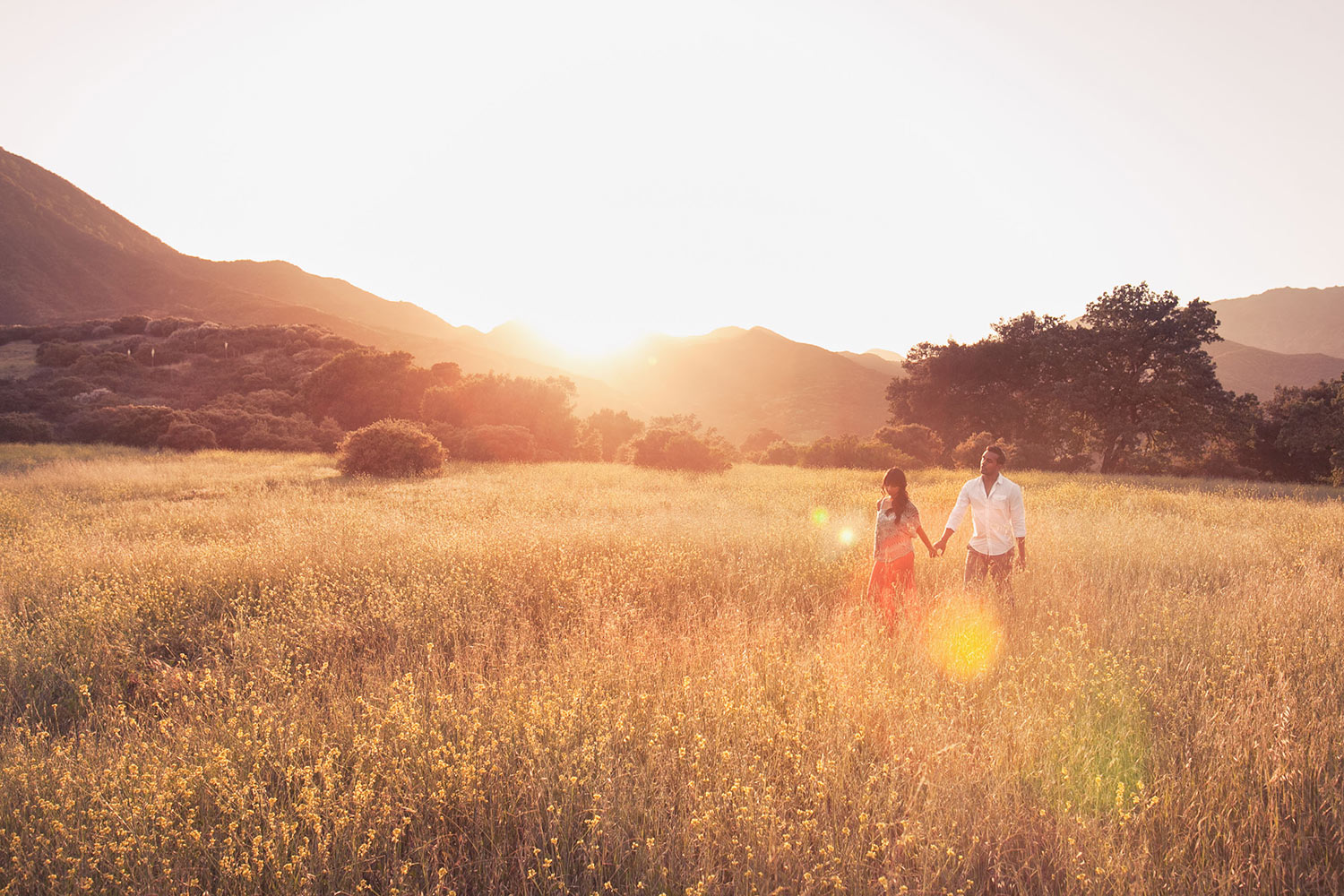 Paramount Ranch engagement photo of couple walking through field at sunset