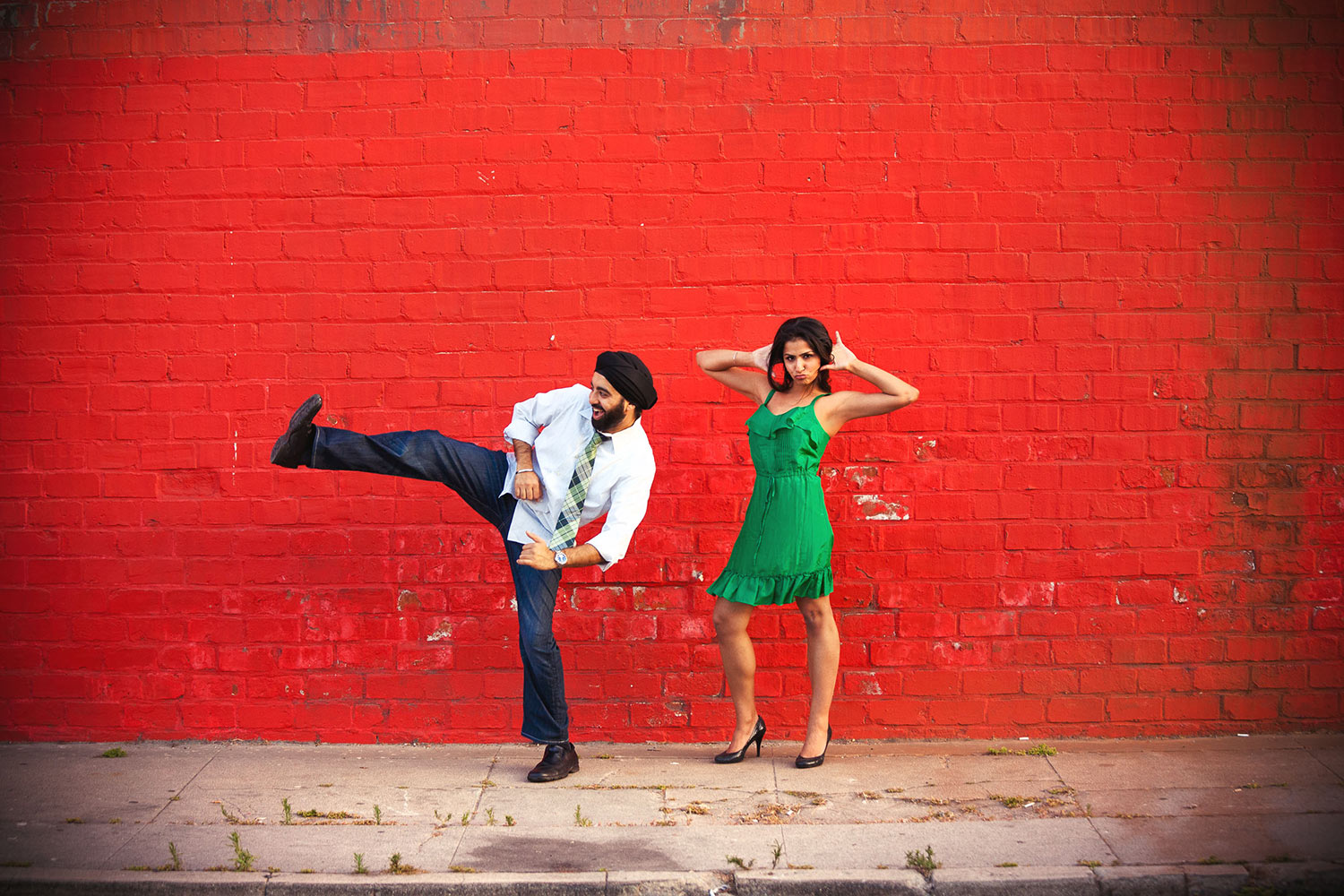 Hilarious South Asian Engagement session photo of couple having fun in front of a bright red wall