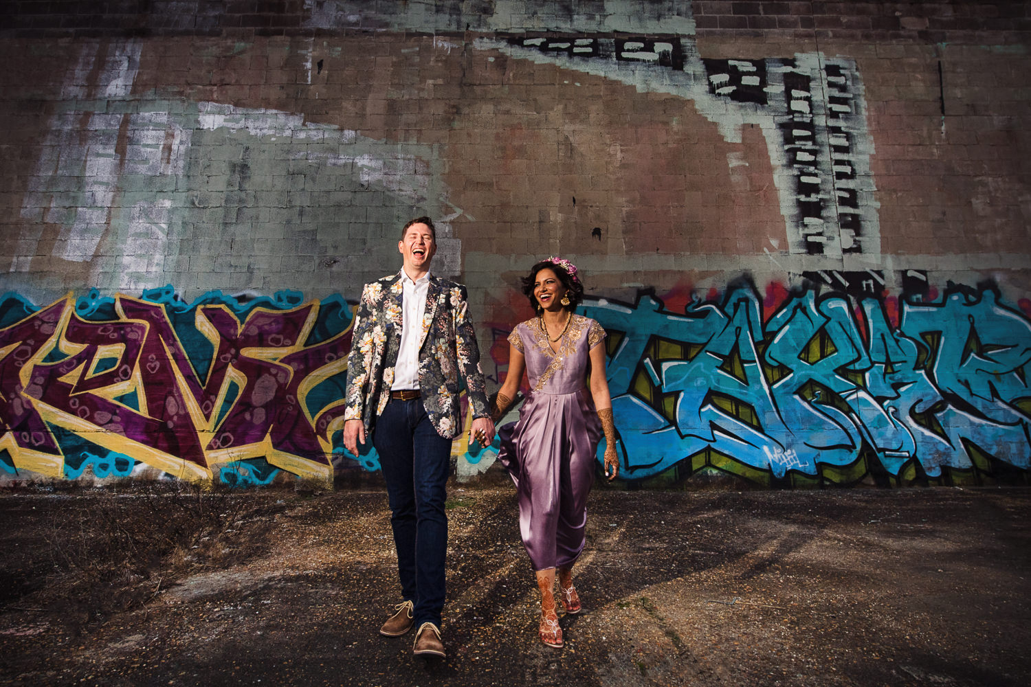 New Orleans Engagement photo of couple running in front of graffiti