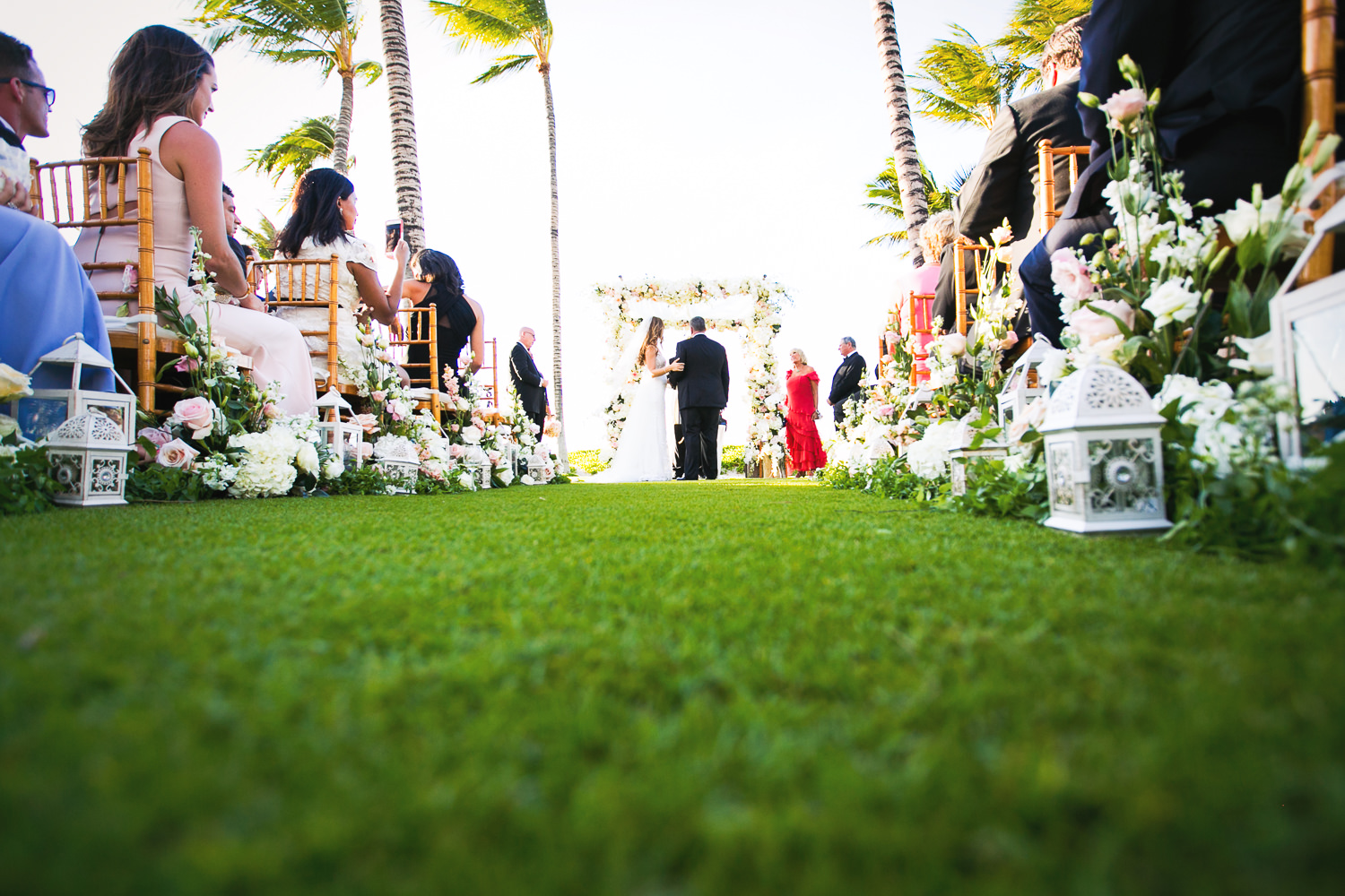 Great low shot in the grass wedding ceremony on the beach at the Four Seasons Hualalai