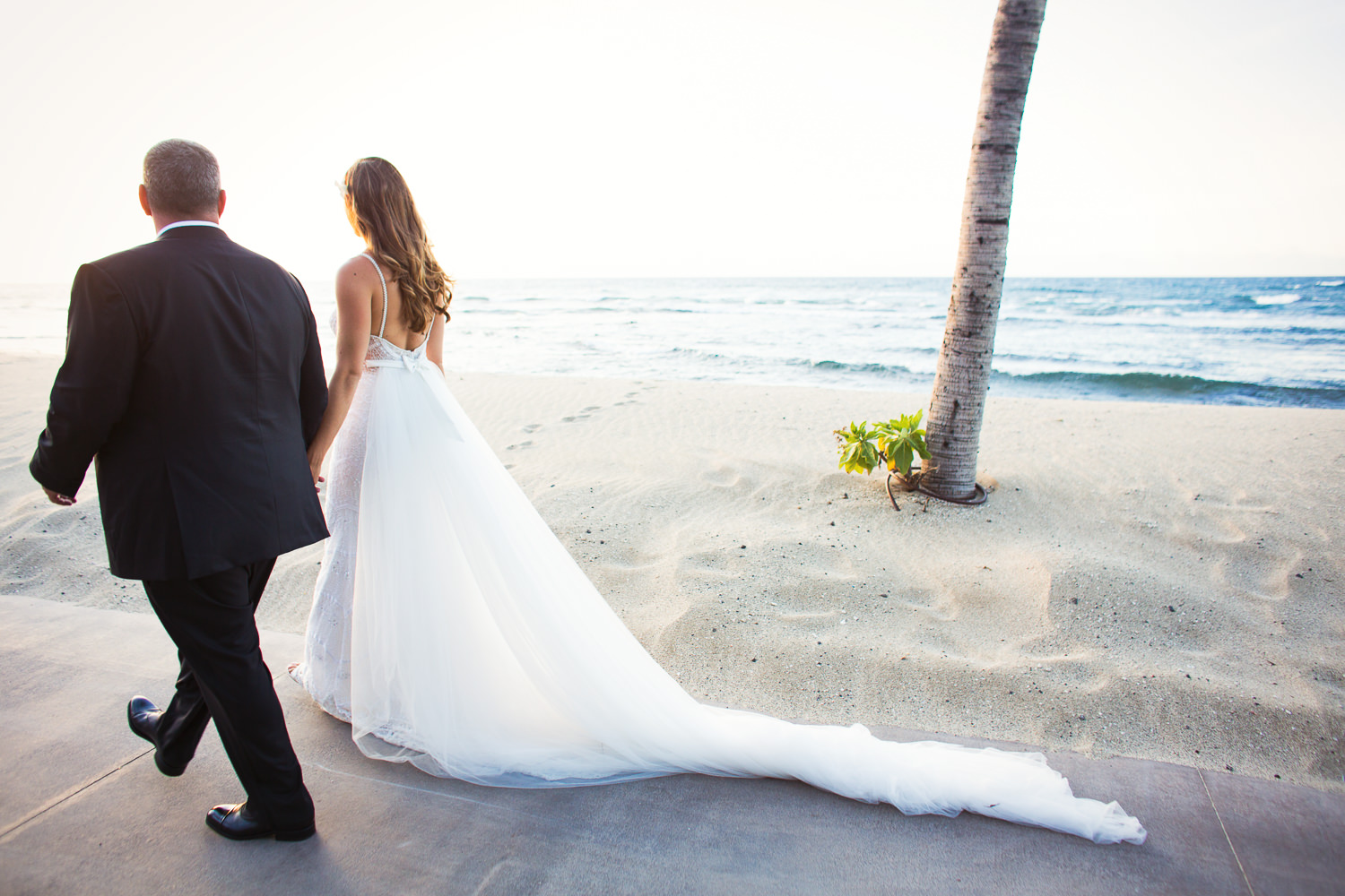 Walking towards the sunset as newlyweds at the Four Seasons Hualalai by Big Island wedding photographer Callaway Gable