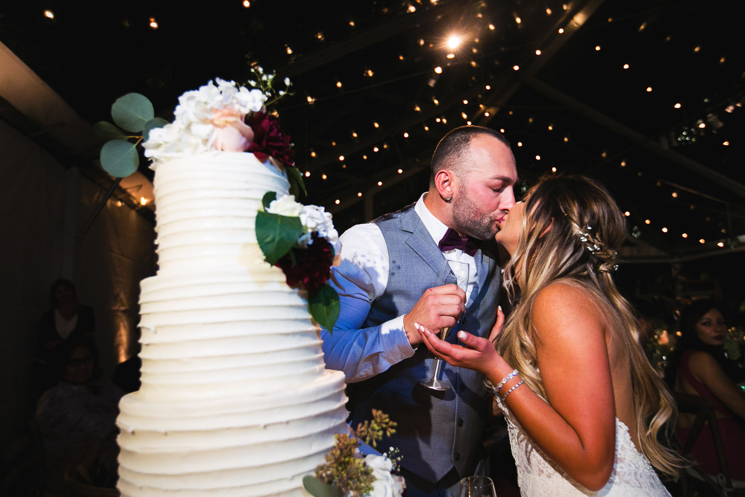 Cutting the cake in the tent in Stacy Porras planned Hummingbird Nest wedding