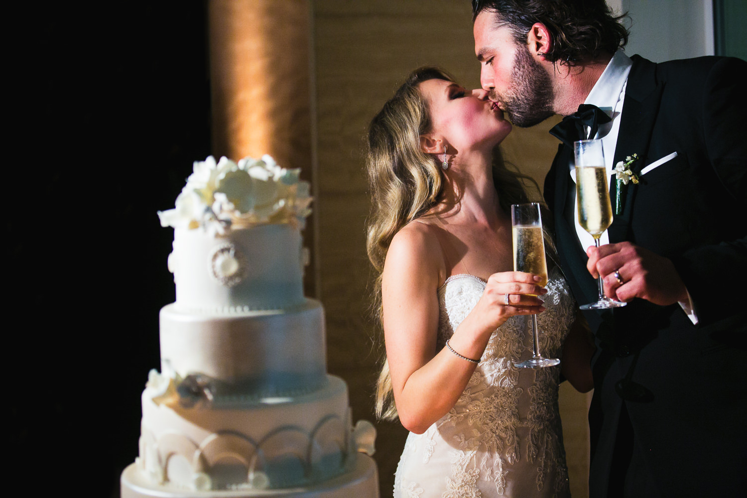 Four Seasons Santa Barbara Wedding - Newly Weds Kissing With Champagne By Cake
