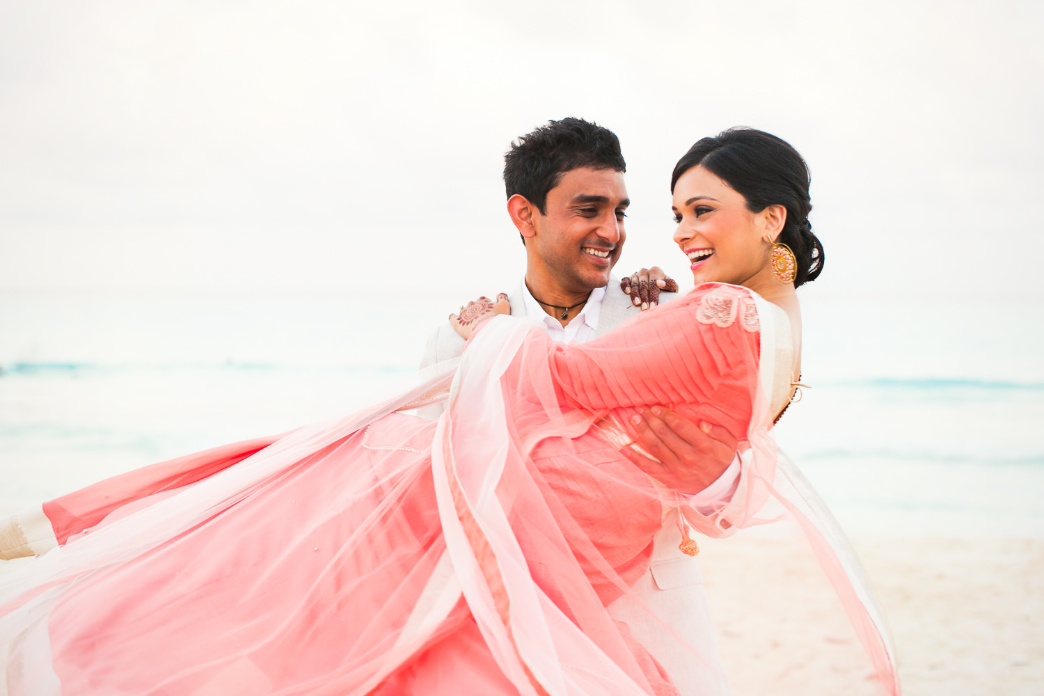 Paradisus Cancun Indian Wedding - Groom carrying happy Bride on the beach