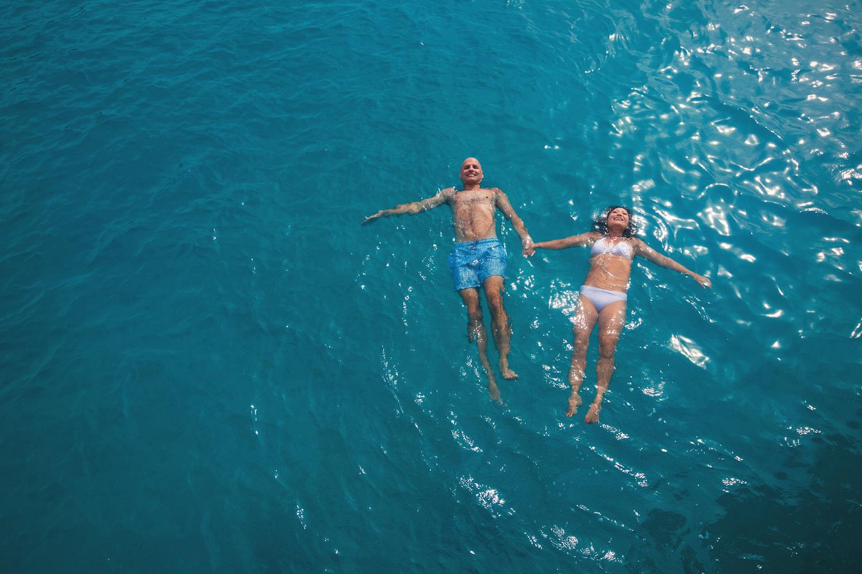 Four Seasons Bora Bora Wedding - Swimming in the water hand in hand