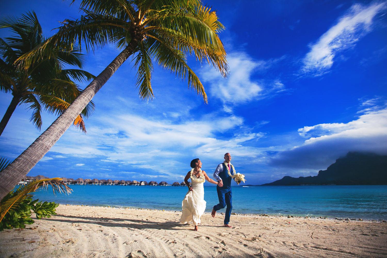 Four Seasons Bora Bora Wedding - Hand in hand running on the beach