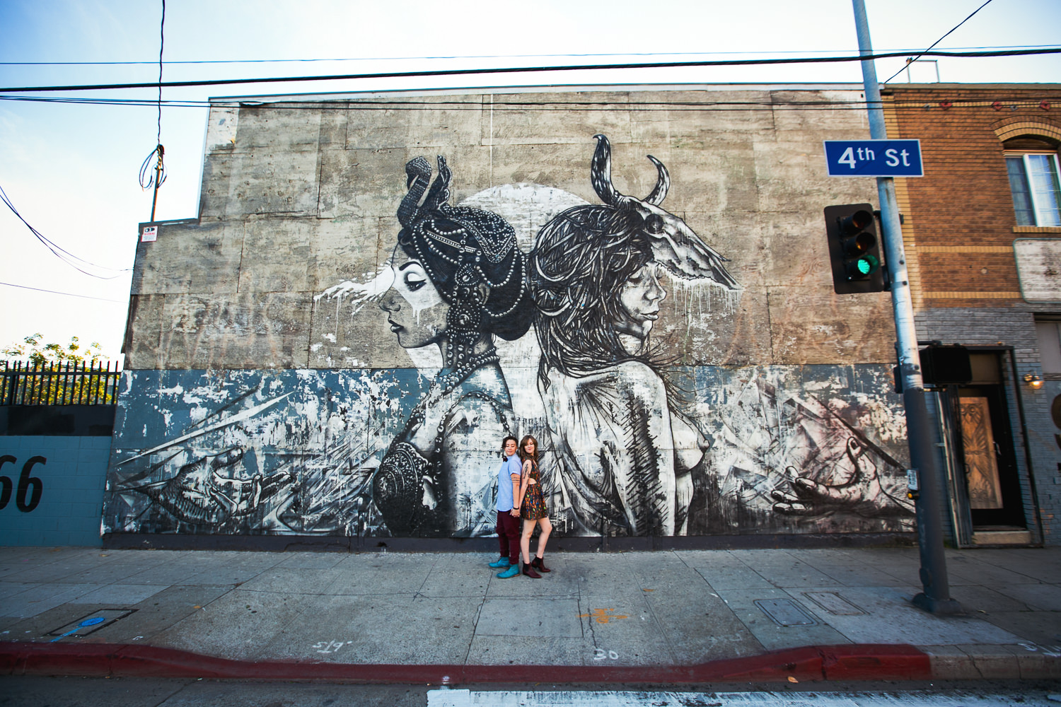 Same Sex Los Angeles Engagement - Back to back as shown in the wall mural