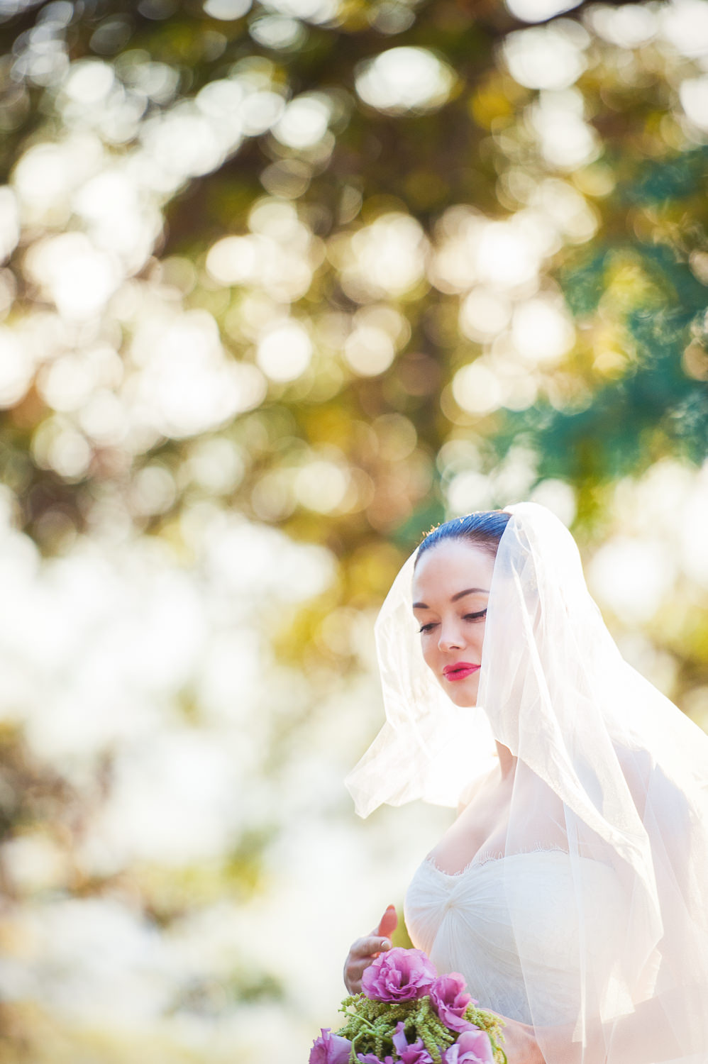 Rose McGowan Wedding at Paramour Estate - Bride under the trees holding her flowers