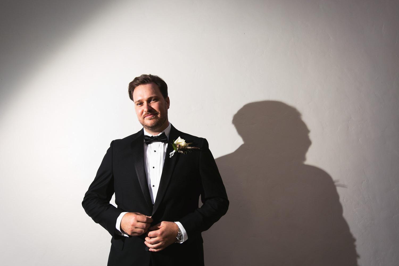 Ebell Long Beach Wedding - Groom up against the wall portrait