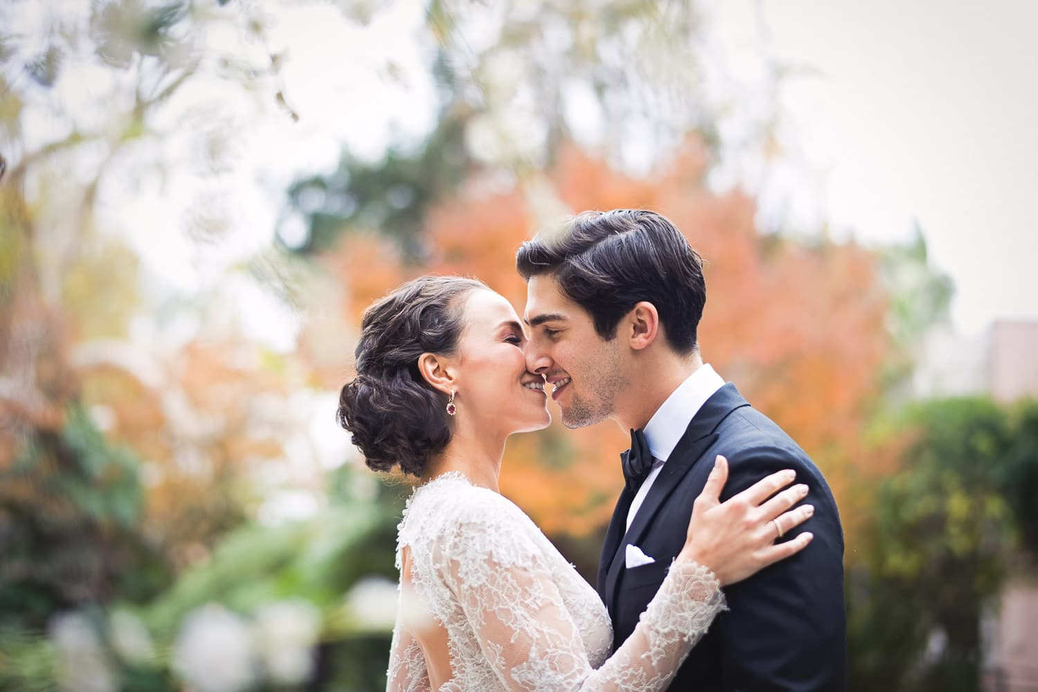 Wedding kiss with fall foliage in background at Hotel Bel-Air