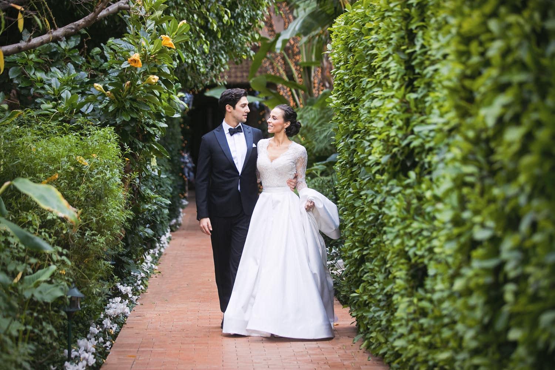 Bride and Groom walking down brick path at Hotel Bel-Air