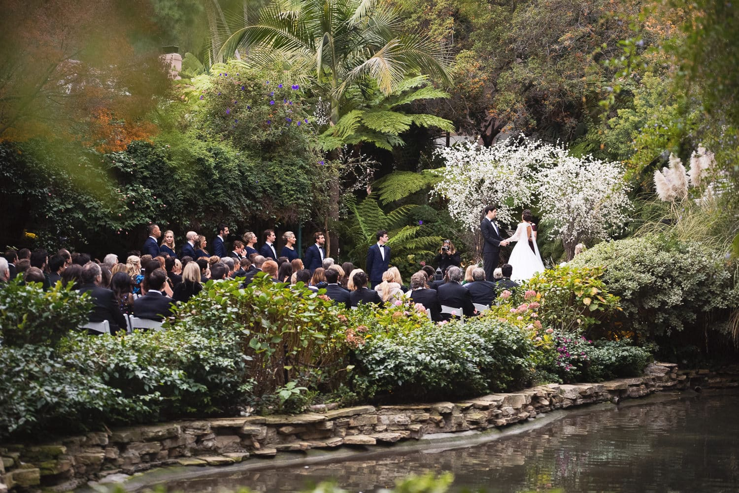 Wide photo of wedding ceremony from across the Hotel Bel-Air pond