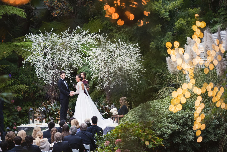 Hotel Bel-Air December wedding ceremony photographed through Christmas decorations on bridge
