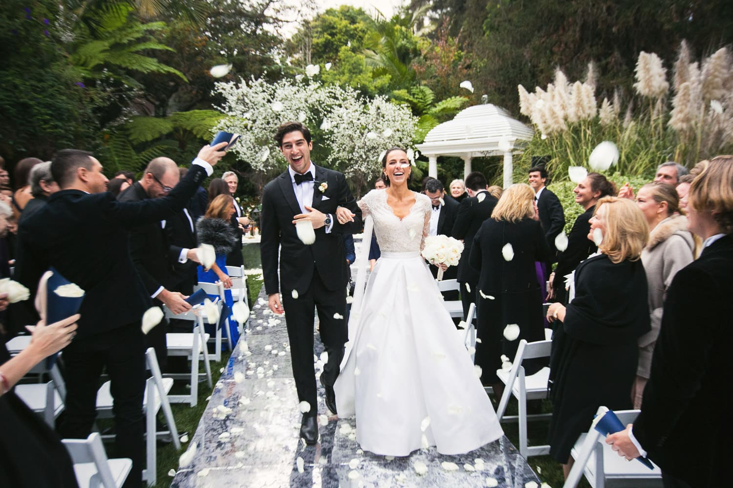 Walking down the aisle with flowers being thrown in the air after they said I do at the Hotel Bel-Air