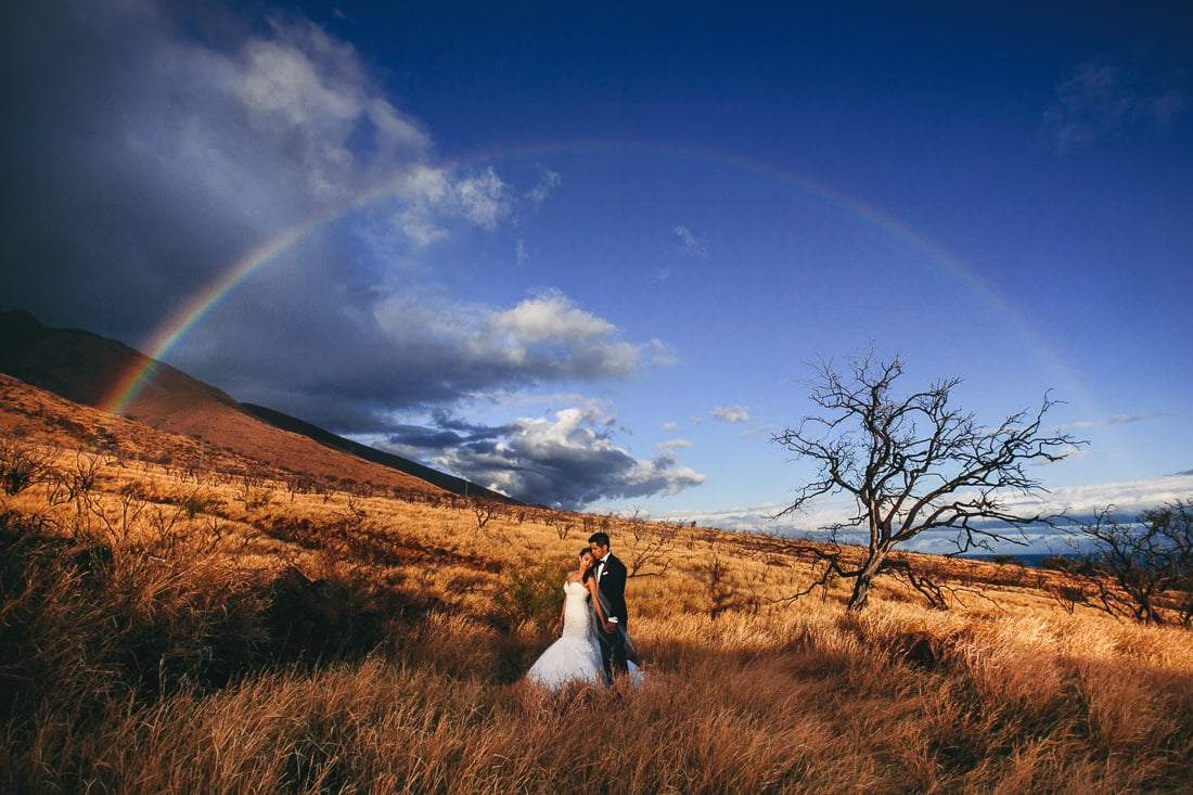 Bride and Groom embracing under a rainbow in Maui