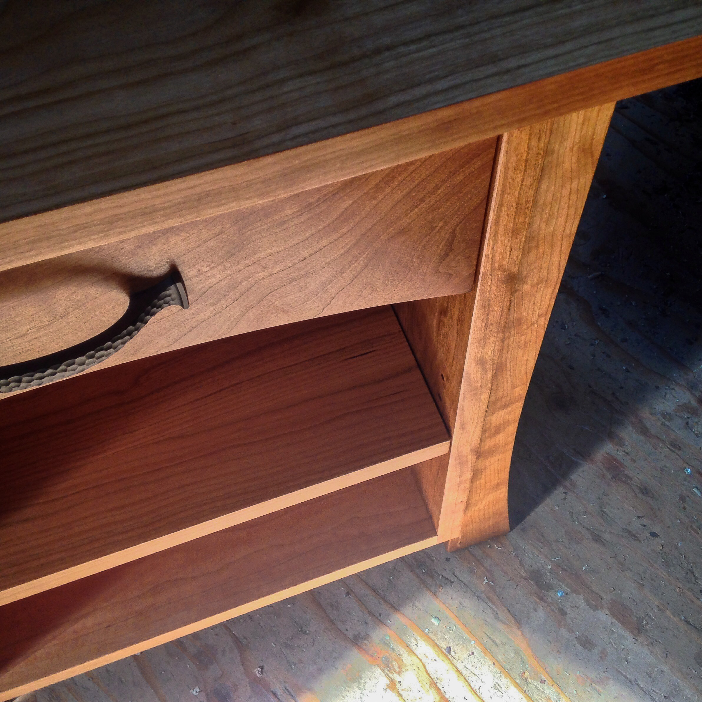 Detail of a cherry night stand with one drawer and adjustable shelf.