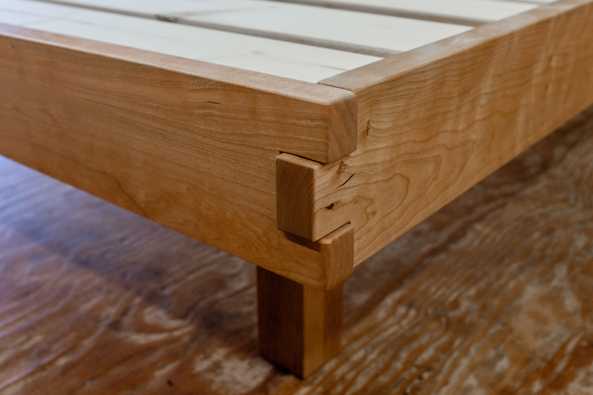 Detail of box joint on cherry foot and side rails, with recessed post.
