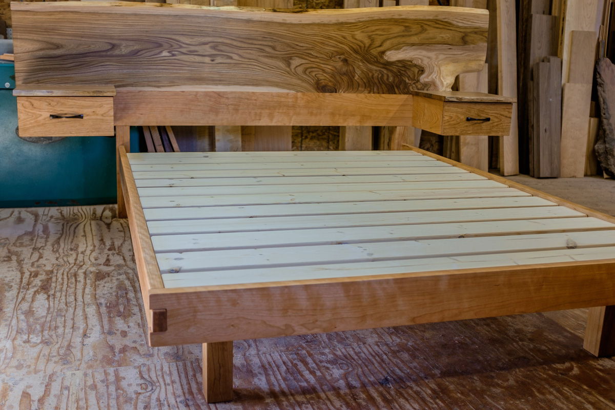 A live edge headboard in ash with attached cherry nightstands featuring elm tops. This bed has a platform construction and a cherry frame, with a unique box jointed foot rail and recessed foot posts.