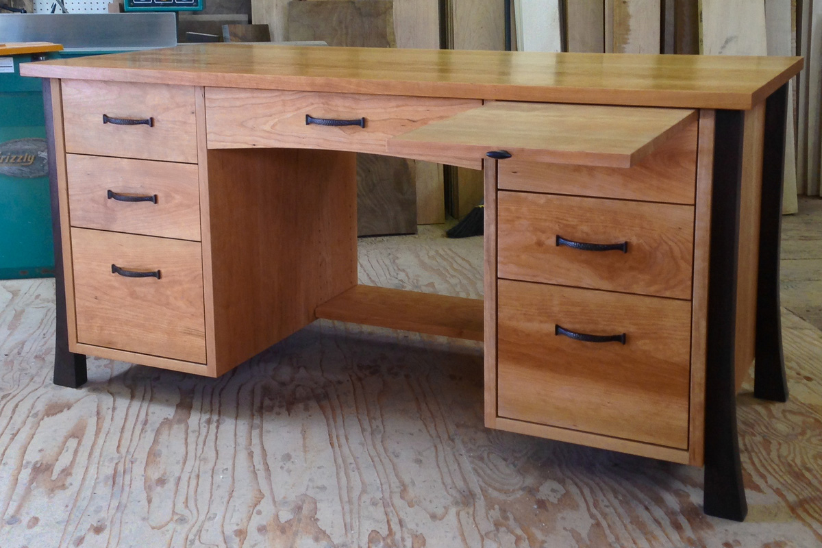 Cherry desk with walnut legs, pencil drawer, two lower file drawers, and pull out writing surface.