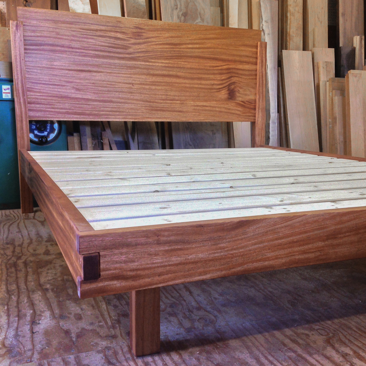 Mahogany platform bed with box joint footboard and recessed legs.