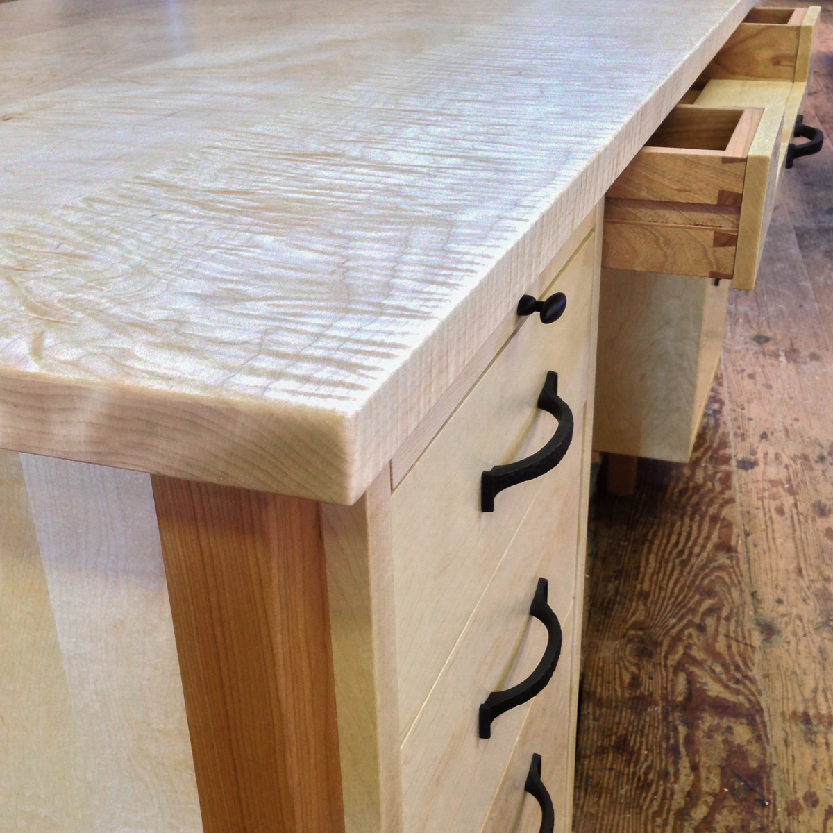 Desk detail with quilted maple top and cherry legs. Featured pull out writing surfaces on top of both banks of drawers and a central sliding keyboard drawer.