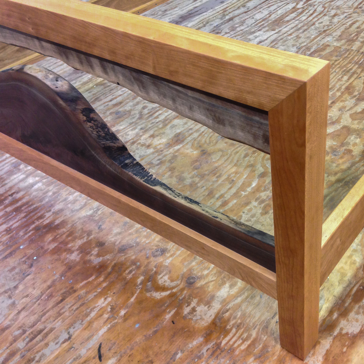 Detail of a footboard with live edge walnut elements in a cherry mitered frame